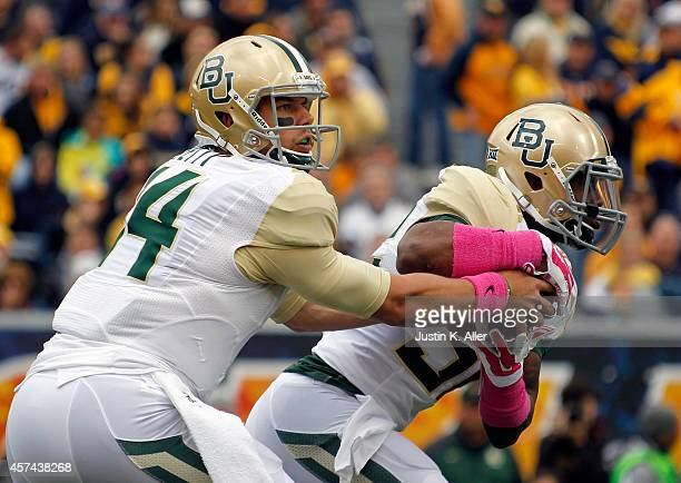 Bryce Petty of the Baylor Bears drops hands off in the first half against the West Virginia Mountaineers during the game on October 18 2014 at...