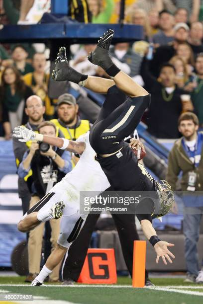Bryce Petty of the Baylor Bears flips into the end zone to score a second-quarter touchdown against the defense of Sean Maag of the UCF Knights...