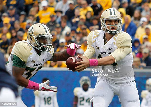 Bryce Petty of the Baylor Bears hands off during the game against the West Virginia Mountaineers on October 18 2014 at Mountaineer Field in...