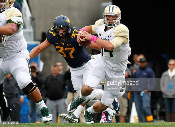 Bryce Petty of the Baylor Bears rushes against Wes Tonkery of the West Virginia Mountaineers during the game on October 18 2014 at Mountaineer Field...