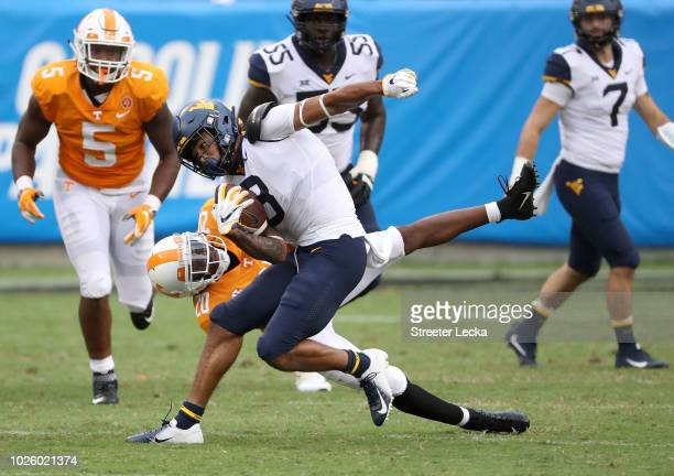 Bryce Thompson of the Tennessee Volunteers tries to tackle Marcus Simms of the West Virginia Mountaineers during their game at Bank of America...