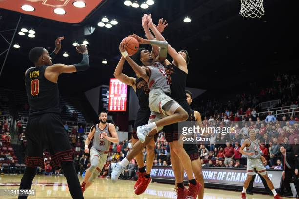 Bryce Wills of the Stanford Cardinal scores the gamewinning basket and is fouled by Nick Rakocevic of the USC Trojans and Derryck Thornton of the USC...