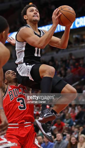 Bryn Forbes of the San Antonio Spurs goes up for a shot over Shaquille Harrison of the Chicago Bulls at the United Center on November 26 2018 in...