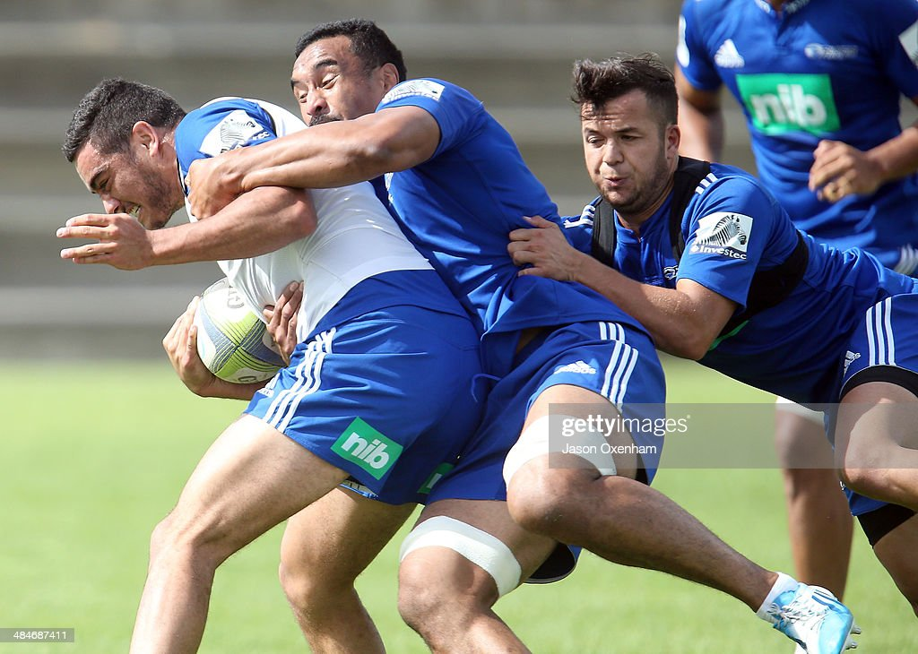 Bryn Hall (L) of the Blues is tackled by Jerome Kaino and Jamison Gibson-Park (R) during an Auckland Blues Super Rugby training session at Unitec on April 14, 2014 in Auckland, New Zealand.