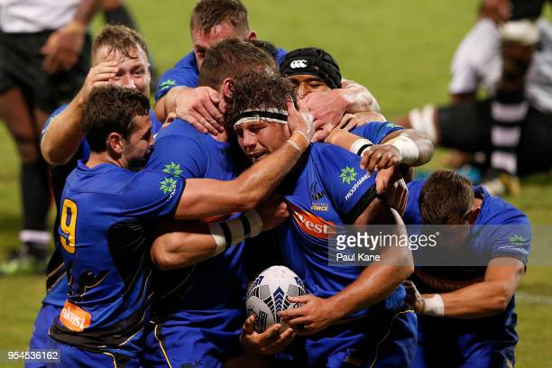 Brynard Stander of the Force is congratulated by team mates after crossing for a try during the World Series Rugby match between the Western Force...