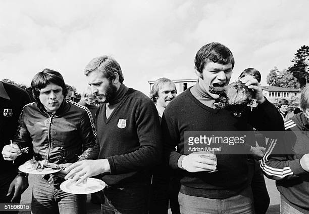 Brynmor Williams and Tony Neary of the British Lions tuck into their meal whilst Fran Cotton Jokes with a pigs head at a barbecue during the British...