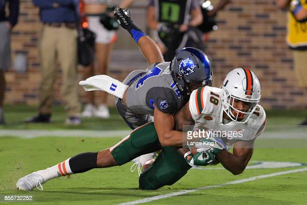 Bryon Fields Jr #14 of the Duke Blue Devils tackles Lawrence Cager of the Miami Hurricanes at Wallace Wade Stadium on September 29 2017 in Durham...