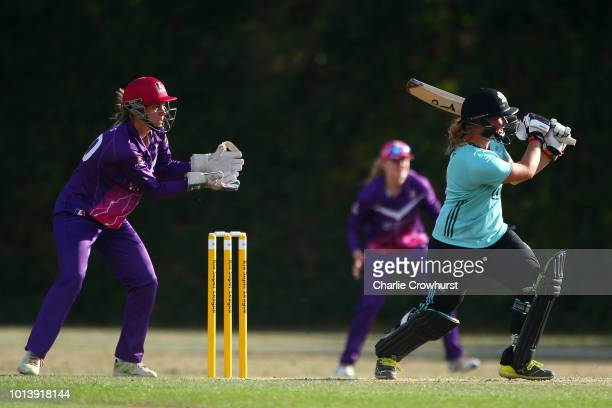 Bryony Smith of Surrey Stars hits out while wicket keeper Amy Jones of Loughborough Lightning looks on during the Kia Super League match between...