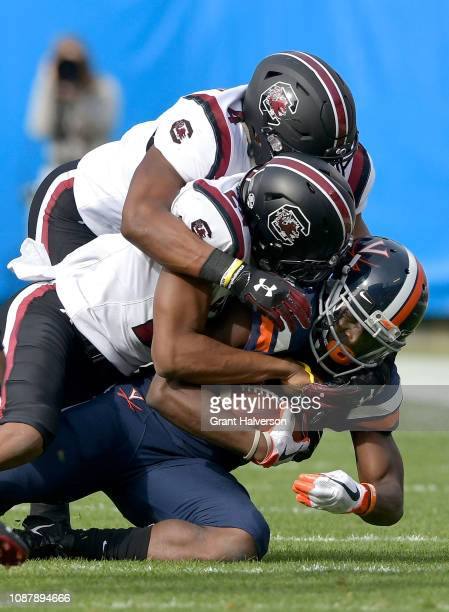 Bryson AllenWilliams and Israel Mukuamu of the South Carolina Gamecocks tackle Olamide Zaccheaus of the Virginia Cavaliers during the first half of...