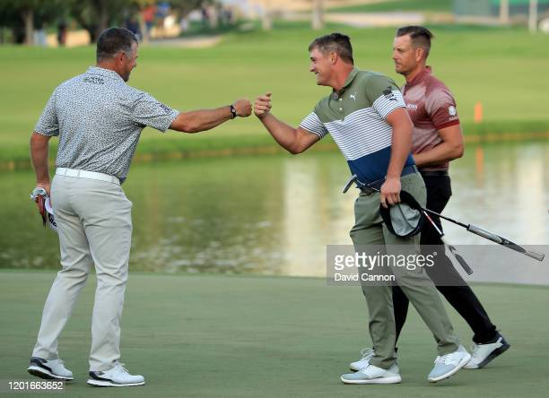 Bryson De Chambeau of the United States shakes 'knuckles' with his playing partner Lee Westwood of England as his other playing partner Henrik...
