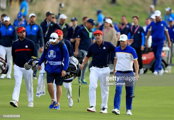 Bryson de Chambeau of the United States walks 18th green with Alex Noren of the European Team as their final game concluded during the final day...