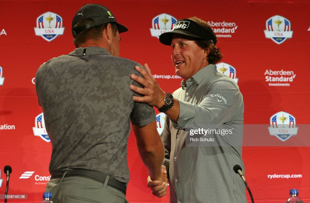 Bryson DeChambeau, left, shakes hands with Phil Mickelson after both were introduced by along with Tiger Woods by U.S. Ryder Cup Team Captain Jim Furyk as the Captain's Picks for the 2018 U.S. team during a press conference at the Philadelphia Marriott West on September 4, 2018 in West Conshohocken, Pennsylvania.