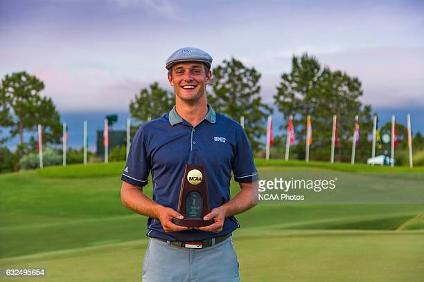 Bryson Dechambeau of Southern Methodist University holds his trophy on the 18th green of the Concession Golf Club in Bradenton, Florida after winning...