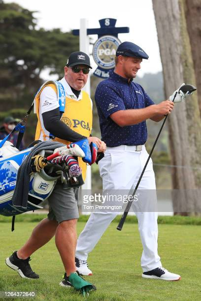 Bryson DeChambeau of the United States affixes his new shaft to his driver head as he walks off the eighth tee with caddie Tim Tucker during the...