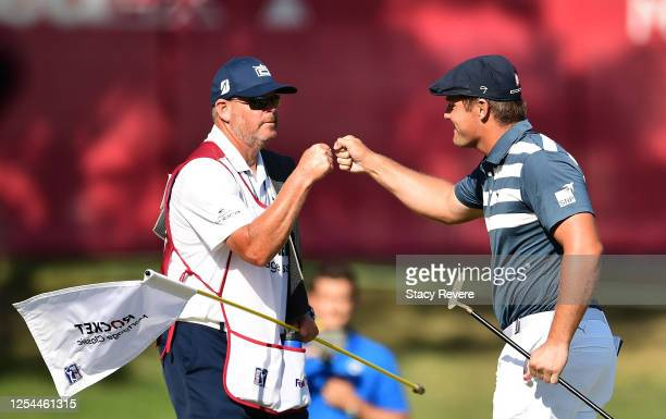 Bryson DeChambeau of the United States and caddie Tim Tucker celebrate on the 18th green on his way to winning during the final round of the Rocket...