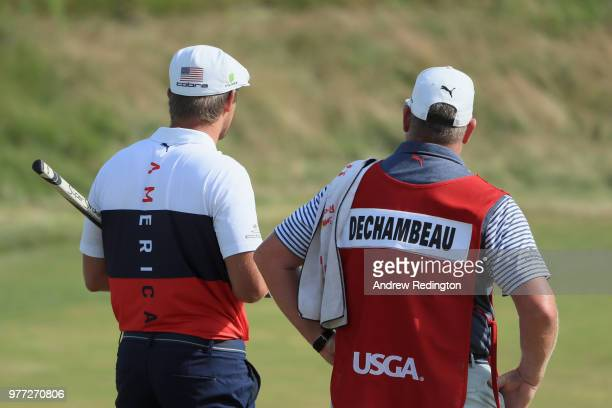 Bryson DeChambeau of the United States and caddie Tim Tucker walk off the 18th green during the final round of the 2018 US Open at Shinnecock Hills...