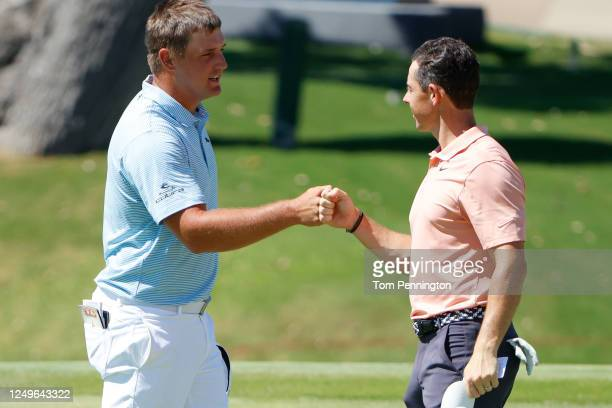 Bryson DeChambeau of the United States and Rory McIlroy of Northern Ireland bump fists after finishing on the 18th green during the final round of...