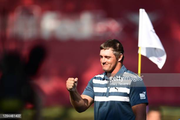 Bryson DeChambeau of the United States celebrates on the 18th green on his way to winning during the final round of the Rocket Mortgage Classic on...