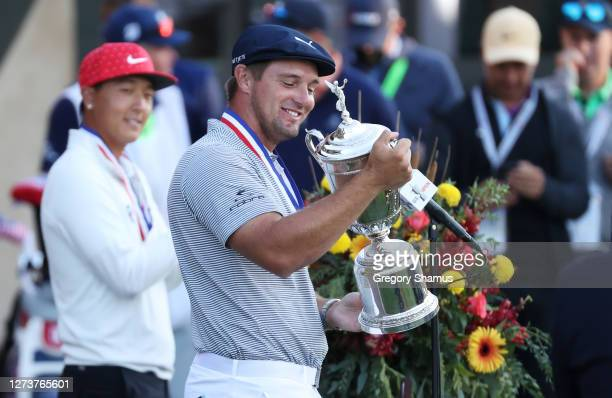 Bryson DeChambeau of the United States celebrates with the championship trophy after winning as low amateur John Pak of the United States looks on...