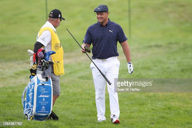 Bryson DeChambeau of the United States hands his broken driver to caddie Tim Tucker on the seventh hole during the first round of the 2020 PGA...
