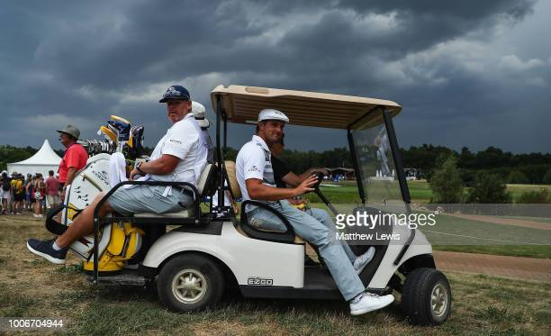 Bryson Dechambeau of the United States is given a lift back into the clubhouse as thunderstorms stop play during day three of the Porsche European...