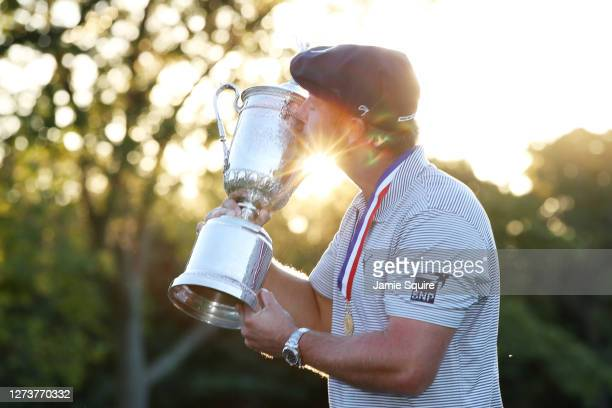 Bryson DeChambeau of the United States kisses the championship trophy in celebration after winning the 120th U.S. Open Championship on September 20,...