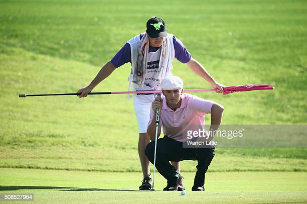 Bryson DeChambeau of the United States lines up a putt on the 7th green with his caddie during the second round of the Omega Dubai Desert Classic at...