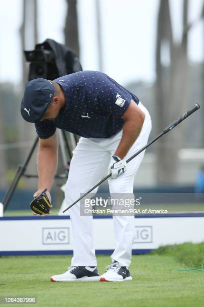 Bryson DeChambeau of the United States picks up his the head of his broken driver on the seventh tee during the first round of the 2020 PGA...