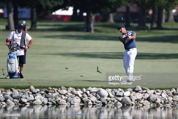 Bryson DeChambeau of the United States plays a shot on the 14th hole as a bird flies past during the final round of the Rocket Mortgage Classic on...