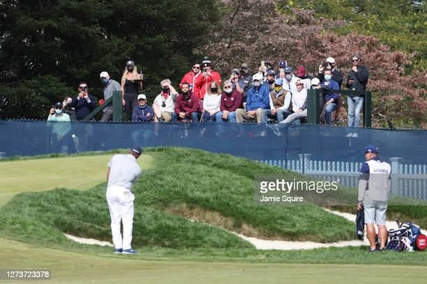 Bryson DeChambeau of the United States plays the third green as a gallery and caddie Tim Tucker look on during the final round of the 120th U.S. Open...