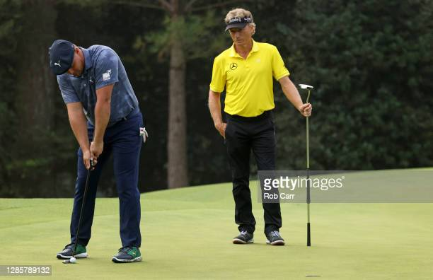 Bryson DeChambeau of the United States putts on the 14th green as Bernhard Langer of Germany looks on during the final round of the Masters at...