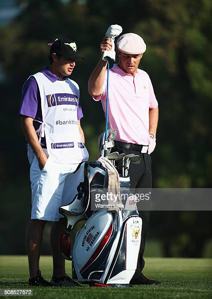 Bryson DeChambeau of the United States talks with his caddie on the 3rd hole during the second round of the Omega Dubai Desert Classic at the...