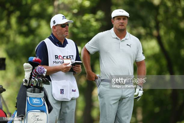 Bryson DeChambeau of the United States talks with his caddie Tim Tucker on the 11th tee during the first round of the Rocket Mortgage Classic on July...