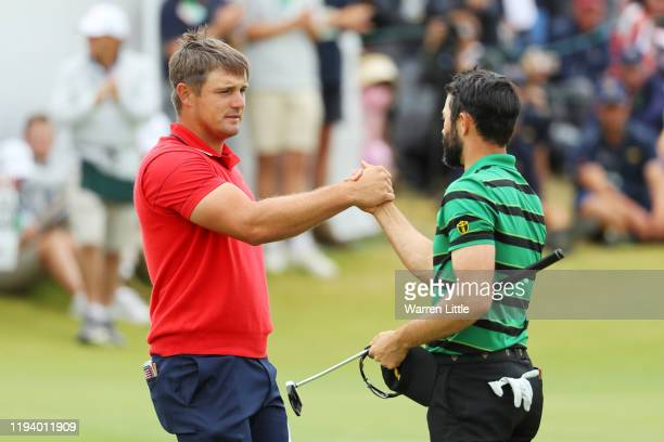 Bryson DeChambeau of the United States team shakes hands with Adam Hadwin of Canada and the International team after they halved their match on the...