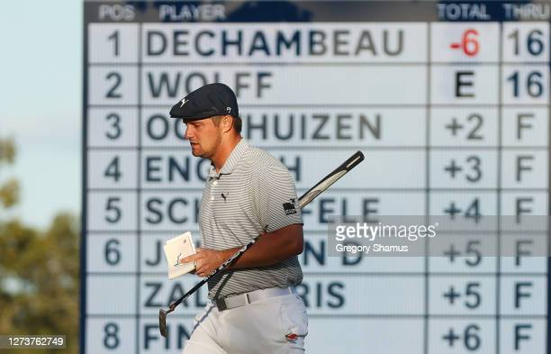 Bryson DeChambeau of the United States walks past a leaderboard on his way to the 17th green during the final round of the 120th U.S. Open...