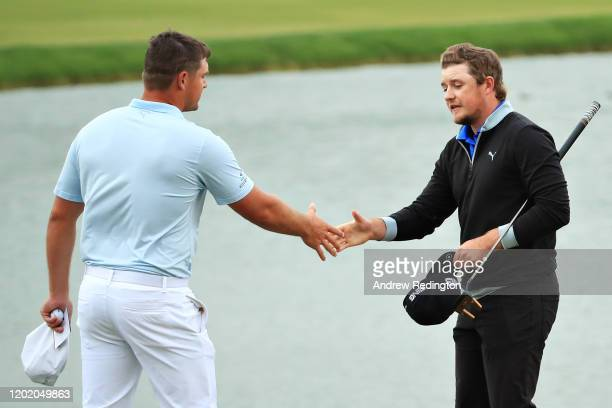 Bryson Dechambeau of United States and Eddie Pepperell of England shake hands on the eighteenth green during Day Four of the Omega Dubai Desert...