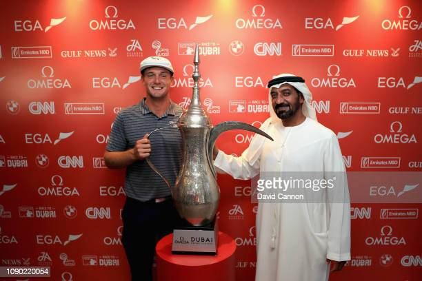 Bryson Dechambeau of United States is presented with the winners trophy by Chairman of Emirates Airlines Sheikh Ahmed bin Saeed Al Maktoum during Day...