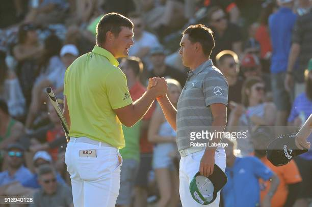 Bryson DeChambeau shakes hands with Rickie Fowler after their round on the 18th hole during the Waste Management Phoenix Open at TPC Scottsdale on...