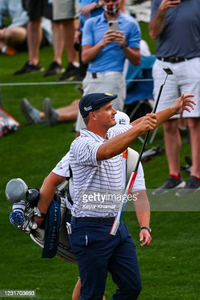 Bryson DeChambeau smiles and raises his arms to acknowledge fans on the 17th hole during the third round of THE PLAYERS Championship on the Stadium...