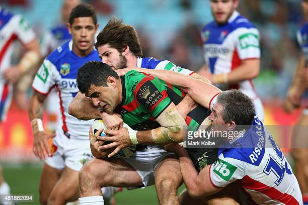Bryson Goodwin of the Rabbitohs is tackled by Jake Mamo and Chris Houston of the Knights during the round 20 NRL match between the South Sydney...