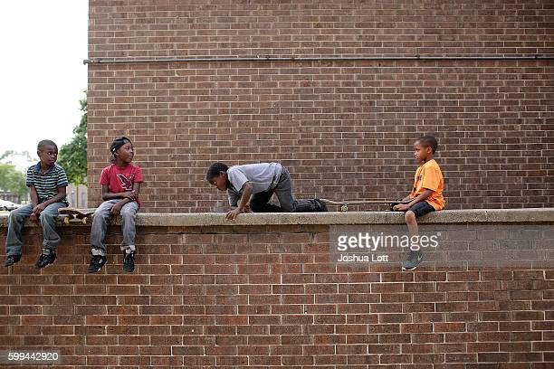 Brysten Edwards second from left sits with other boys on a wall ledge at the West Calumet Housing Complex on September 4 2016 in East Chicago Indiana...