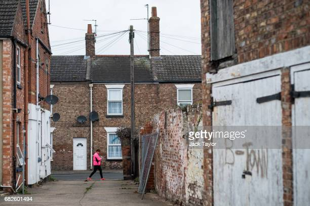 'BTown' is seen scratched into paint work on a garage door as a woman walks through a residential street on May 13 2017 in Boston United Kingdom The...