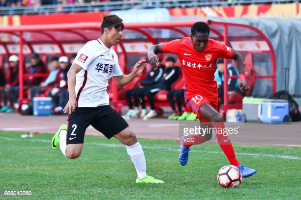Bubacarr Trawally of Yanbian Funde and Zhao Mingjian of Hebei CFFC vie for the ball during the 5th round match between Yanbian Funde FC and Hebei...