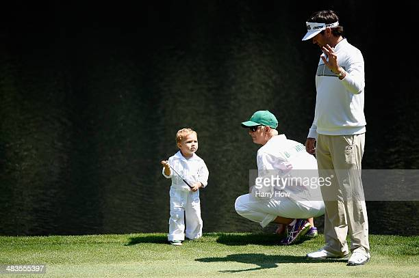 Bubba and Angie Watson wait with their son Caleb on the ninth green during the Par 3 Contest prior to the start of the 2014 Masters Tournament at...