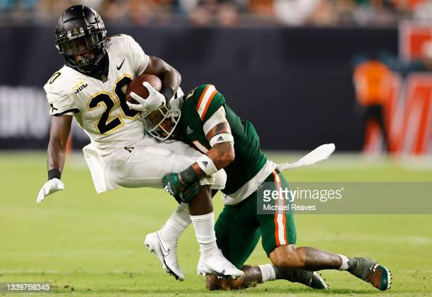 Bubba Bolden of the Miami Hurricanes tackles Nate Noel of the Appalachian State Mountaineers during the first quarter at Hard Rock Stadium on...