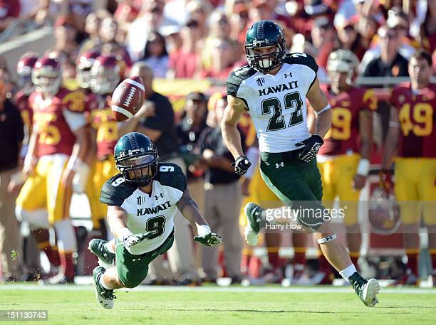 Bubba PoueuLuna dives for the ball in front of Leroy Lutu of the Hawaii Warriors after breaking up a pass during a 4910 loss to the USC Trojans at...