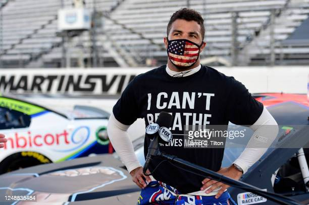 Bubba Wallace driver of the Richard Petty Motorsports Chevrolet wears a I Can't Breathee Black Lives Matter tshirt under his fire suit in solidarity...