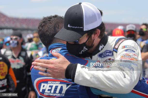 Bubba Wallace driver of the Victory Junction Chevrolet and Corey LaJoie driver of the WallStBookiecom Ford embrace prior to the NASCAR Cup Series...