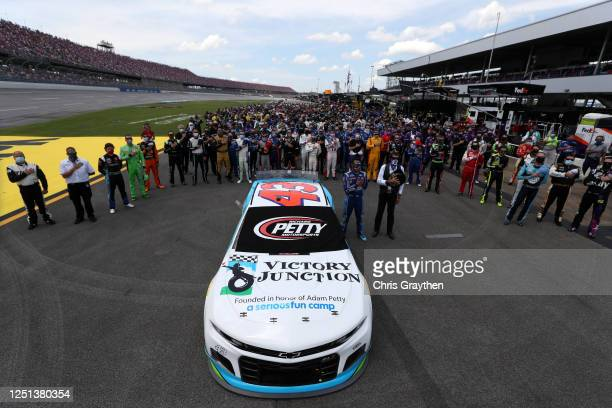 Bubba Wallace, driver of the Victory Junction Chevrolet, and team owner, and NASCAR Hall of Famer Richard Petty stand for the national anthem prior...
