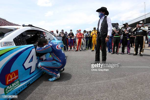 Bubba Wallace driver of the Victory Junction Chevrolet kneels as team owner and NASCAR Hall of Famer Richard Petty and NASCAR drivers stand in...